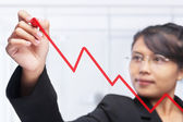Asian businesswoman drawing graph with red felt tip pen — Stock Photo