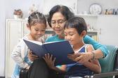 Grandma and grandchildren reading book together — Stock Photo