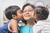 Grandmother being kissed by grandchildren at home — Stock Photo