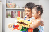 Asian sibling playing hand puppet — Stock Photo