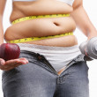 Fat woman with unzup jeans holding apple and weight on each hand — Stock Photo