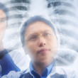 Two Asian doctor examining xray result — Stock Photo #11047324