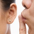 Man shhing woman on her ear — Stock Photo