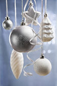 Silver and white Christmas ornaments over blue — Stock Photo