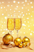 Champagne and golden Christmas ornaments — Stock Photo
