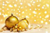 Adornos de navidad dorados con desdibujan luz — Foto de Stock