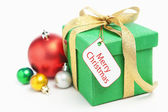 Green Christmas gift with ornament and tag — Stock Photo