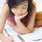 Little girl writing her diary — Stock Photo #11054138
