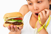Young female surprisingly looking at burger — Stockfoto