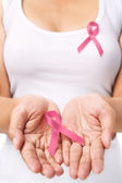 Woman showing pink ribbon to support breast cancer cause — Zdjęcie stockowe