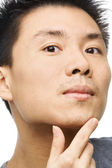 Asian man looking his unshaved chin — Stock Photo