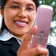 Stock Photo: Young Asibusinesswomusing text messaging