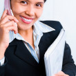 Young businesswoman smiling to camera while listening to her cel — Stock Photo #11069925