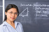 Student pose in front of blackboard — Stock Photo