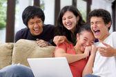 Multi étnica estudiantes riéndose de algo en portátil — Foto de Stock