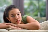Female teenager on sofa at home — Stock Photo