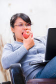 Young woman eating apple while looking at her laptop — Stock Photo