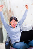 A young woman expressing her joy looking at her laptop at home — Stock Photo