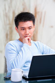 Young Chinese man thinking in front of his laptop — Stock Photo