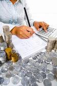 女性の周りの多くのコインと会計働いて — ストック写真