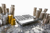 Calculator between pile of coins — Stock Photo