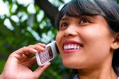 Beautiful woman on the phone in garden area — Stock Photo