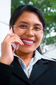 Young Asian businesswoman facing camera whileon the phone — Стоковое фото