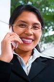 Jovem empresária asiática enfrentando câmera whileon o telefone — Foto Stock