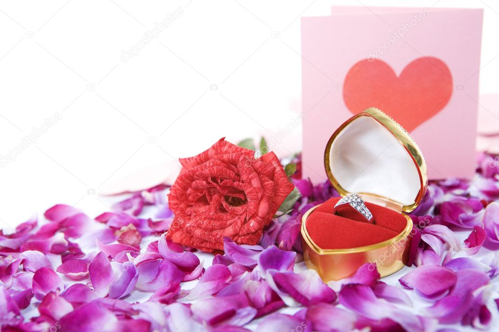 Ring in container with single rose and a valentine card paced together above rose petal with with copy space on the upper right side of the image. — Stock Photo #11069771