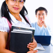 Female scholar holding book and man in background sitting — Foto Stock