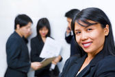 Young Asian Businesswoman smiling to camera with other bu — Stock Photo