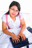 Female scholar typing while looking at camera — Stok fotoğraf