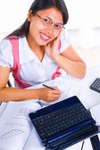 Female scholar looking at camera while studying — Стоковое фото