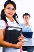 Weibliche gelehrte hält buch und mann im hintergrund sitzen — Stockfoto