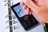Using stylus on touch screen cell phone — Stock Photo