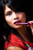 Young woman using lipstick brush — Stock Photo