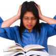 A stressful female student facing a lot of books that she must read. — Stock Photo #11080513