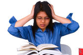 A stressful female student facing a lot of books that she must read. — Stock Photo