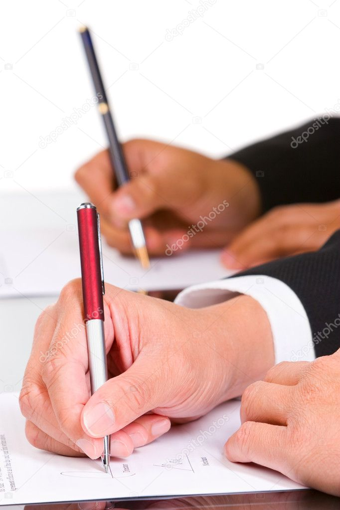 Two hand is signing the document, focused mainly on the front hand. — Stock Photo #11080354