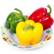 Green red and yellow paprika(capsicum) on plate — Stock Photo