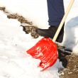 Close-up of man shoveling snow with red shovel - Stock Photo