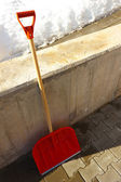 Red wooden shovel leaning against the wall — Stock Photo