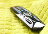 Black remote control on a green blanket — Stock Photo