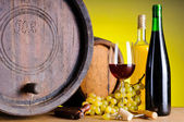Still life with wine, grapes and barrels — Stock Photo
