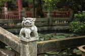 Lion shaped sculpture over banisters in corner of pond in courtyard. — Stock Photo