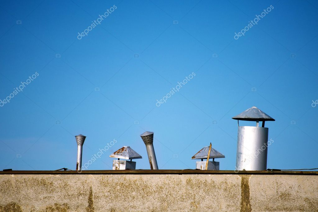 Old rusty chimneys on building rooftop  — Stock Photo #11351236