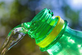 Close up of water flowing from green bottle — Stock Photo