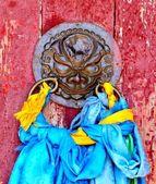 Monastery door with prayer scarves — Stock Photo