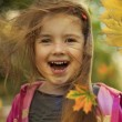 Stock Photo: Little girl in autumn with falling leaves and hair in wind