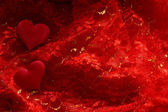Hearts on red satin background — Stock Photo